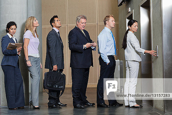 Businesspeople waiting in queue for elevator
