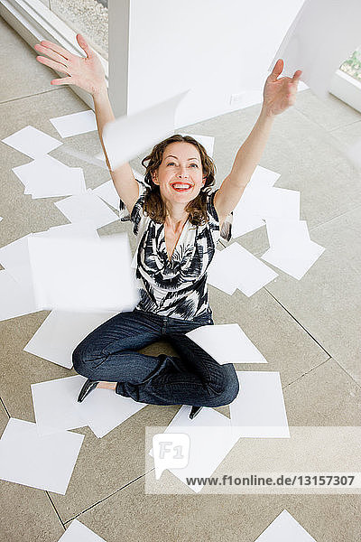 Woman throwing paper sheets into the air