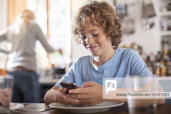 Teenage boy using smartphone at dining table