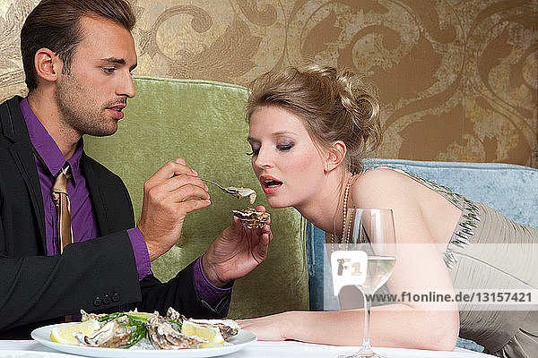 Man feeding girlfriend oysters