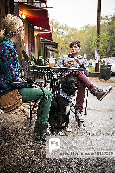 Couple with dog having coffee at sidewalk cafe,  Savannah,  Georgia,  USA