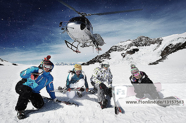Group of skiers with rescue helicopter overhead