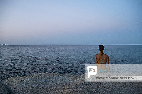 Young woman sitting on rock  looking out to sea  Costa rei  Sardinia  Italy