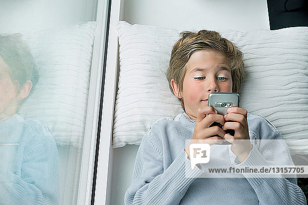 Boy lying down with mobile phone