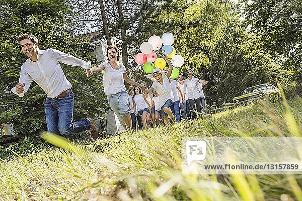 Group of people running through forest  boy holding bunch of balloons