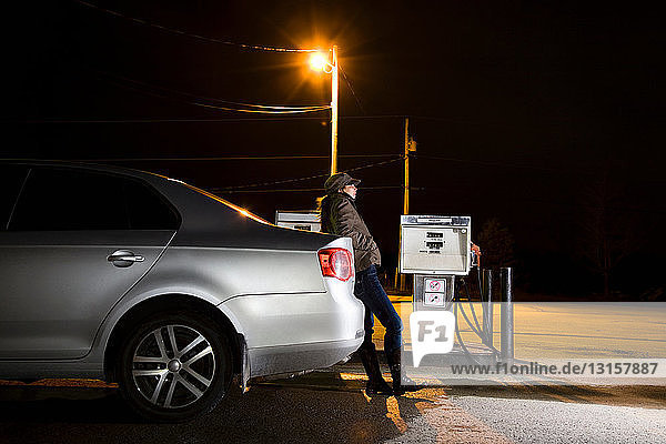 Woman refueling car at night