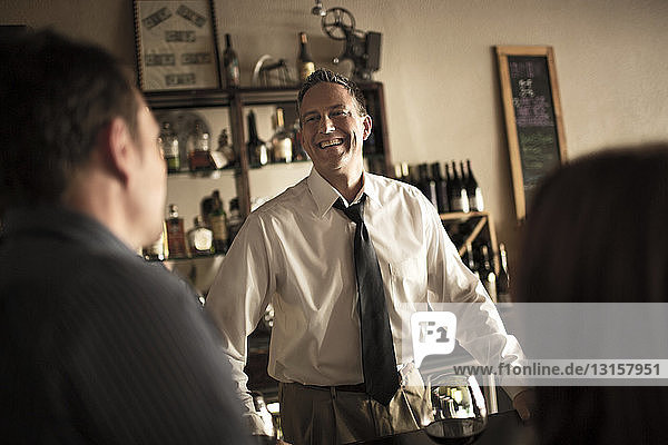 Bartender chatting with customers in wine bar