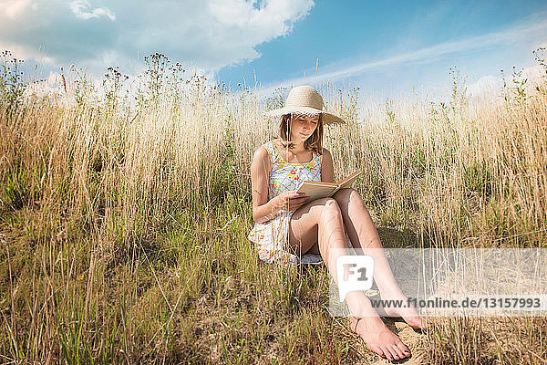 Adolescent girl in sunhat reading story book