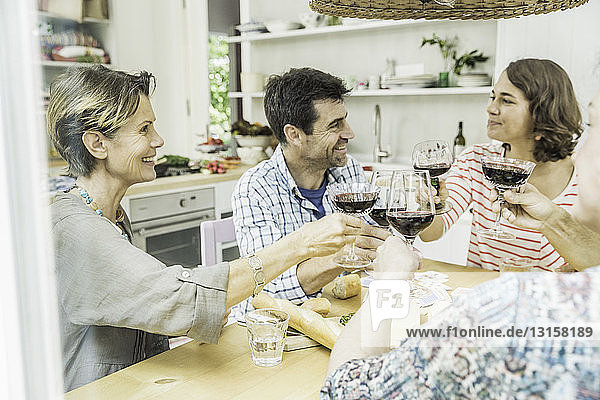 Adult friends making a toast with wine at dining table