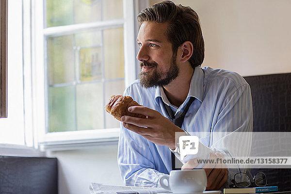 Portrait of man having croissant for breakfast