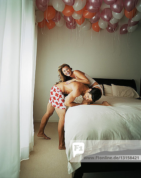 Smiling couple wrestling on bed