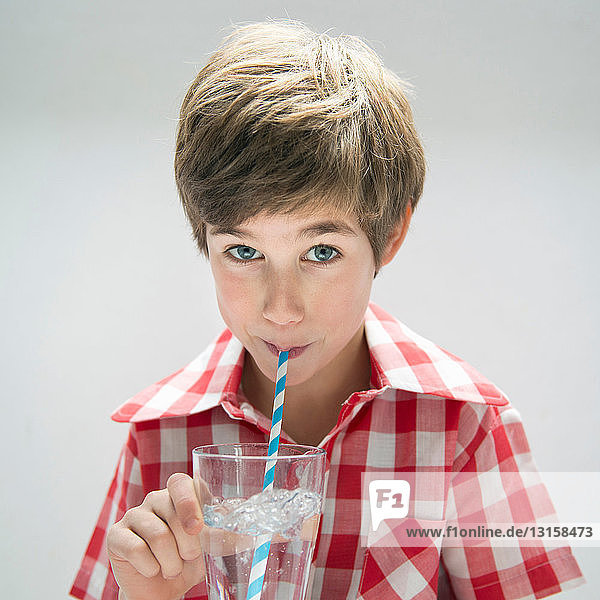 Boy drinking water with straw