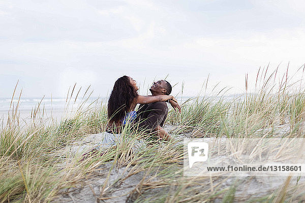 Couple fooling around in sand dunes  laughing
