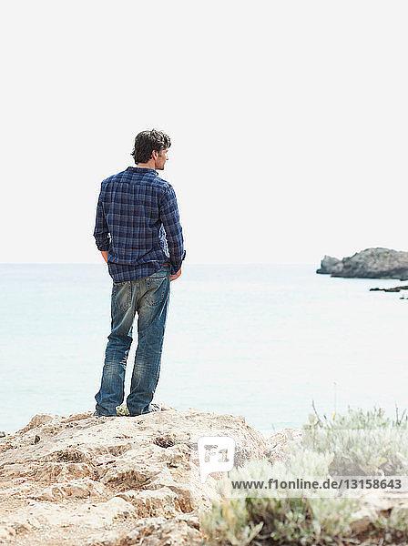man looking at coastline
