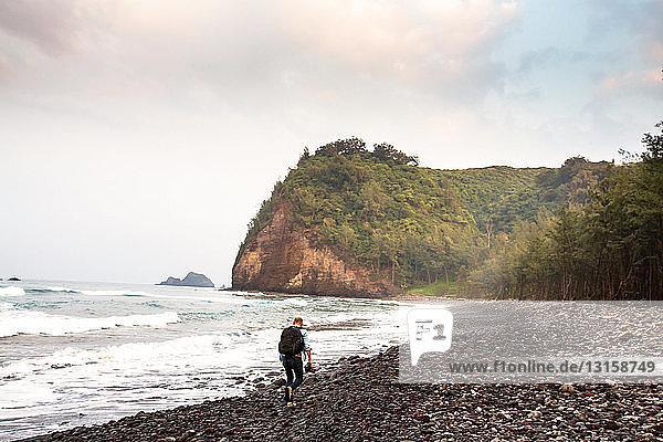 Mid adult man hiking along beach