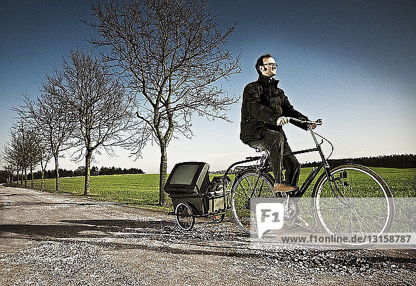 Man riding bicycle with carriage on country road  Ringsted  Denmark