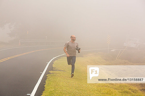 Mid adult man running along roadside with camera