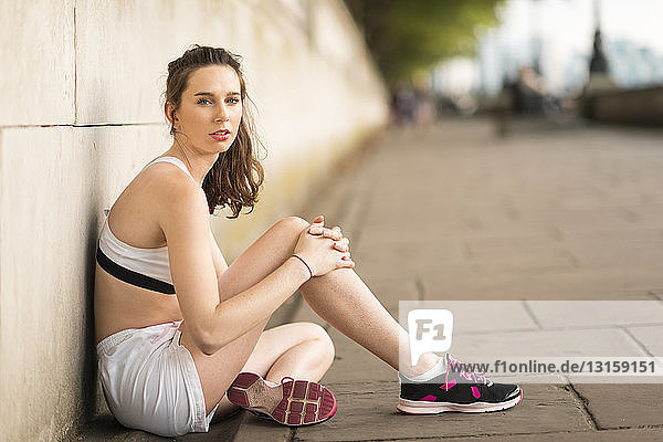 Portrait of young female runner sitting on riverside