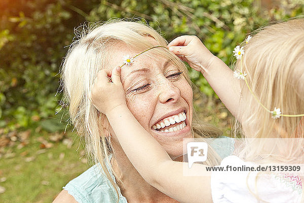 Close up of female toddler placing daisy chain in mother's hair in garden