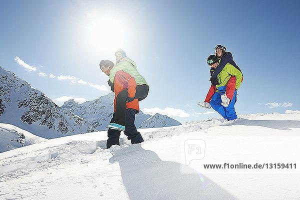 Friends giving piggy backs in snow  Kuhtai  Austria