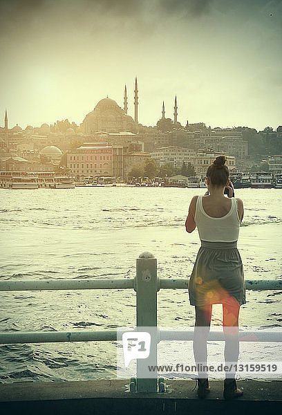 Rear view of female tourist photographing the Bosphorus and Hagia Sophia church  Istanbul Turkey