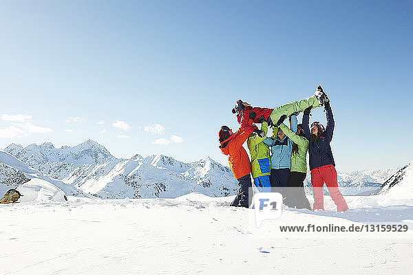 Friends lifting young woman in snow  Kuhtai  Austria
