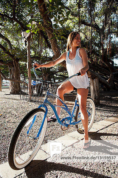 Woman sitting on bicycle in park