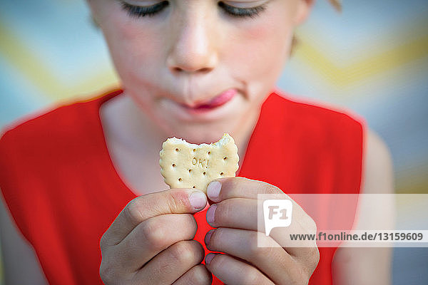 'Boy holding biscuit that says ''OK!'''