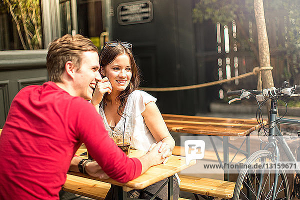 Couple sitting face to face in beer garden holding hands