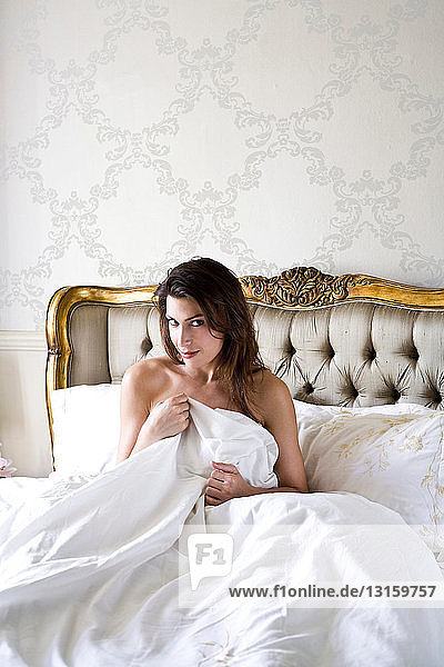 woman sitting in bed looking whimsical