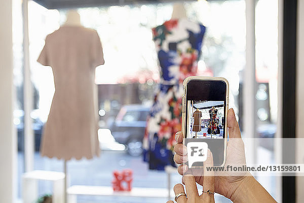 Mature woman taking photograph of dress in clothes shop  using smartphone