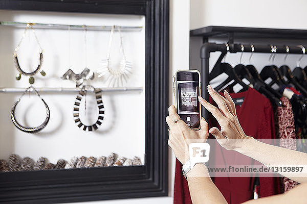 Mature woman taking photograph of jewellery in fashion shop  using smartphone