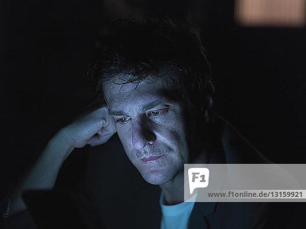 Mid adult man using digital tablet at night  face illuminated