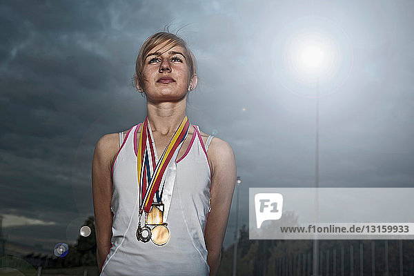 portrait of female athlete with medals