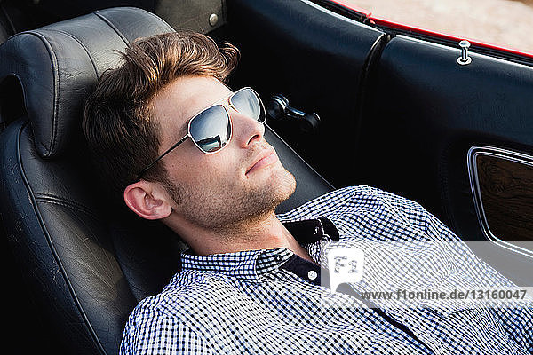 man lying in front seat of car