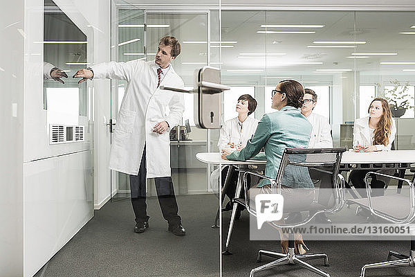 Man wearing lab coat pointing to screen in conference room  four colleagues watching