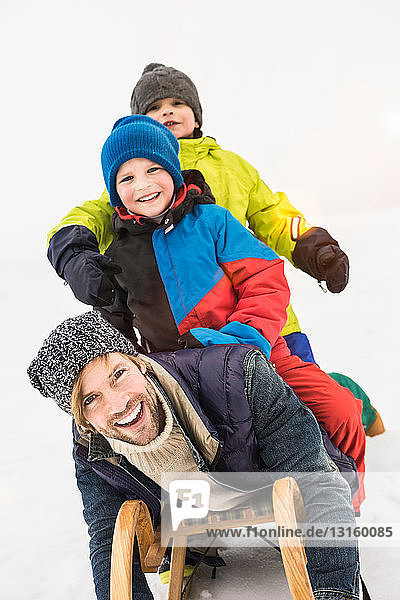 Father with two boys on toboggan in snow Father with two boys on toboggan in snow