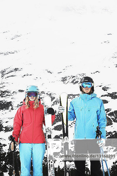 Young people wearing skiwear carrying skis