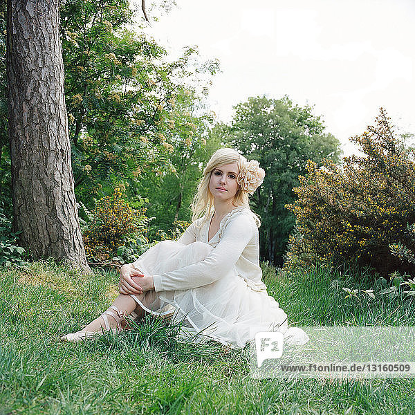 Woman wearing white dress sitting on grass