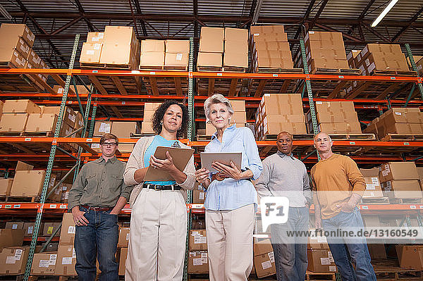 Portrait of warehouse workers in front of boxes