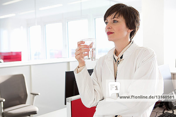 Woman holding glass of water in office