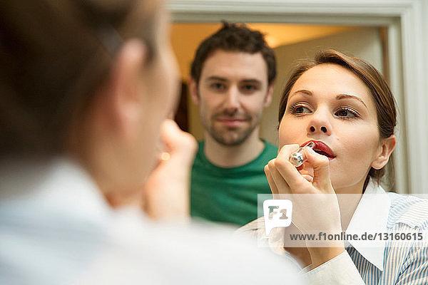 Young woman applying lipstick in bathroom mirror  man watching