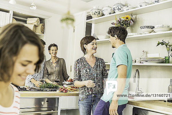 Five adult friends chatting and preparing food in kitchen
