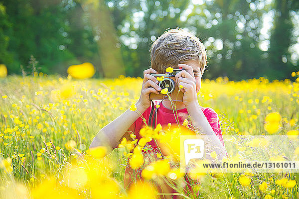 Boy standing in long grass taking photograph