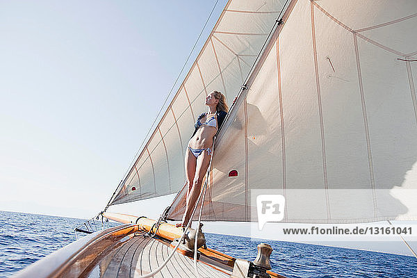 woman leaning at the sails of a boat