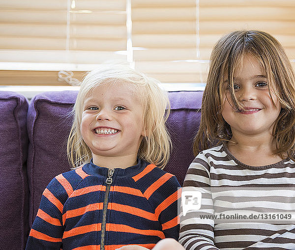 Portrait of young boy and girl  sitting on sofa  smiling