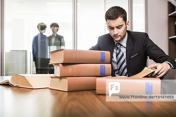 Male lawyer working at desk with books