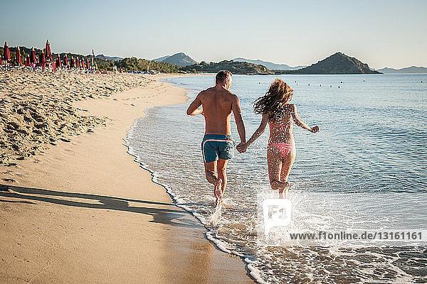 Young couple running in sea  Castiadas  Sardinia  Italy