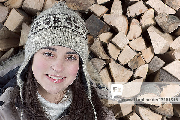 Young woman in front of wood smiling