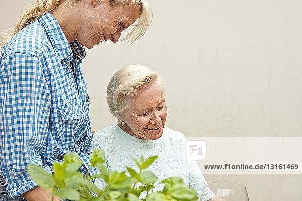 Senior woman and granddaughter chatting at garden table
